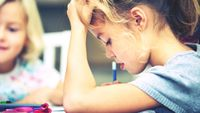 An elementary student working on an assignment, thinking hard