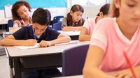 A classroom full of diverse students writing at their desks