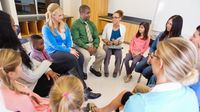 A group of parents, teachers, and students talking in a circle