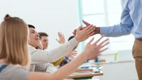 A teacher high-fiving his students