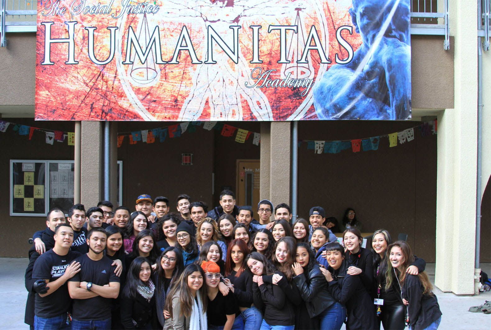 Senior mentors stand with Navarro in front of Social Justice Humanitas Academy.