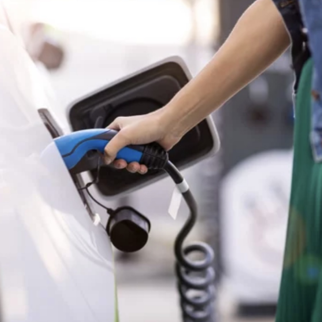 A white woman's arm holding and plugging in an electric car charger