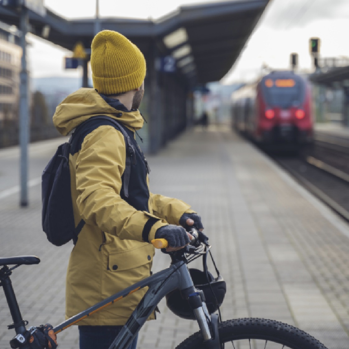 A white man in a tin jacket and hat stands with a bike on a light rail platform
