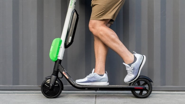 Scooter with man's legs and feet on it, indicating he is riding it