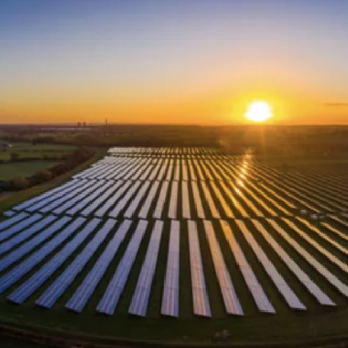 A field of solar panels with the sun setting in the background.
