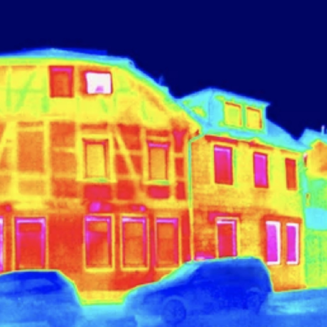 Infrared image of heat loss from the walls and windows of two houses.