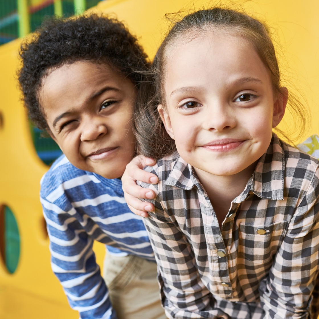 A black boy and white girl stand together in front of a yellow play structure.