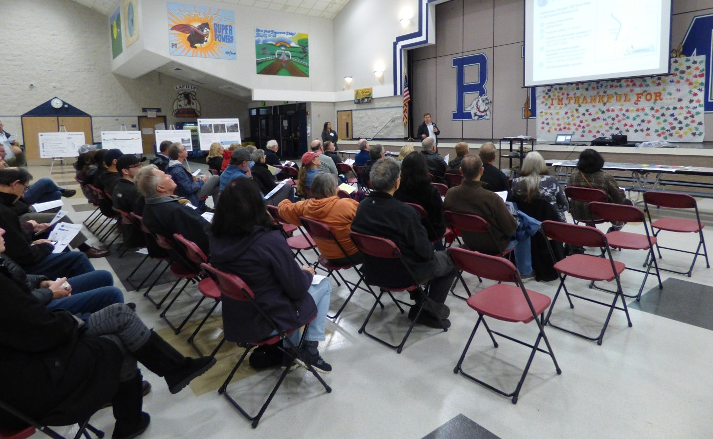 Community meeting at a school auditorium. Audience of about 30 to 40 people are looking forward at project presentation.