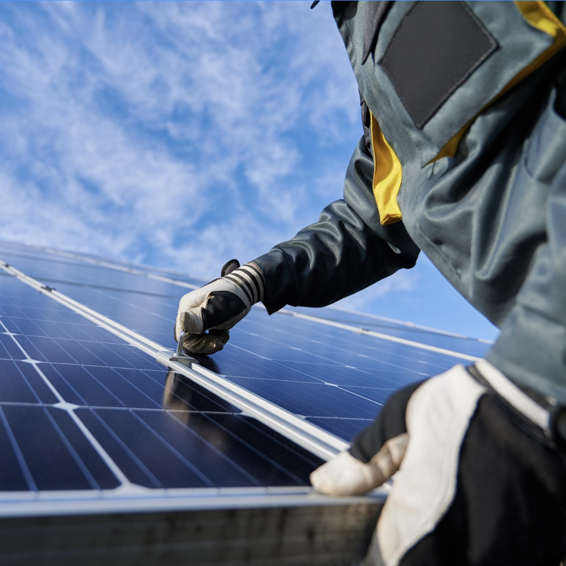 A worker wearing protective gloves connects two solar panels together in a large array.