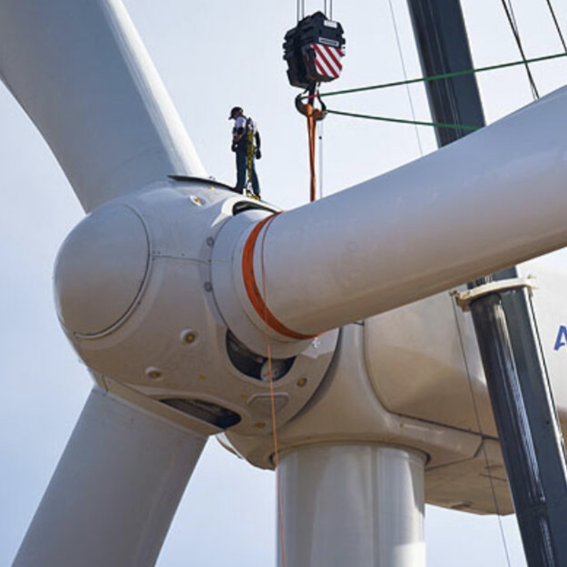 A worker stands on top of a wind turbine under construction.
