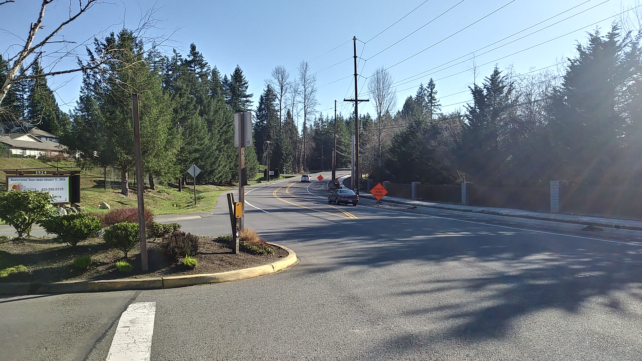 Section of Issaquah-Pine Lake Road with three lanes that curve up a hill. There is one lane oncoming, a center median for a small section of the road and two lanes going away from the camera. Two cars are driving away up the hill.