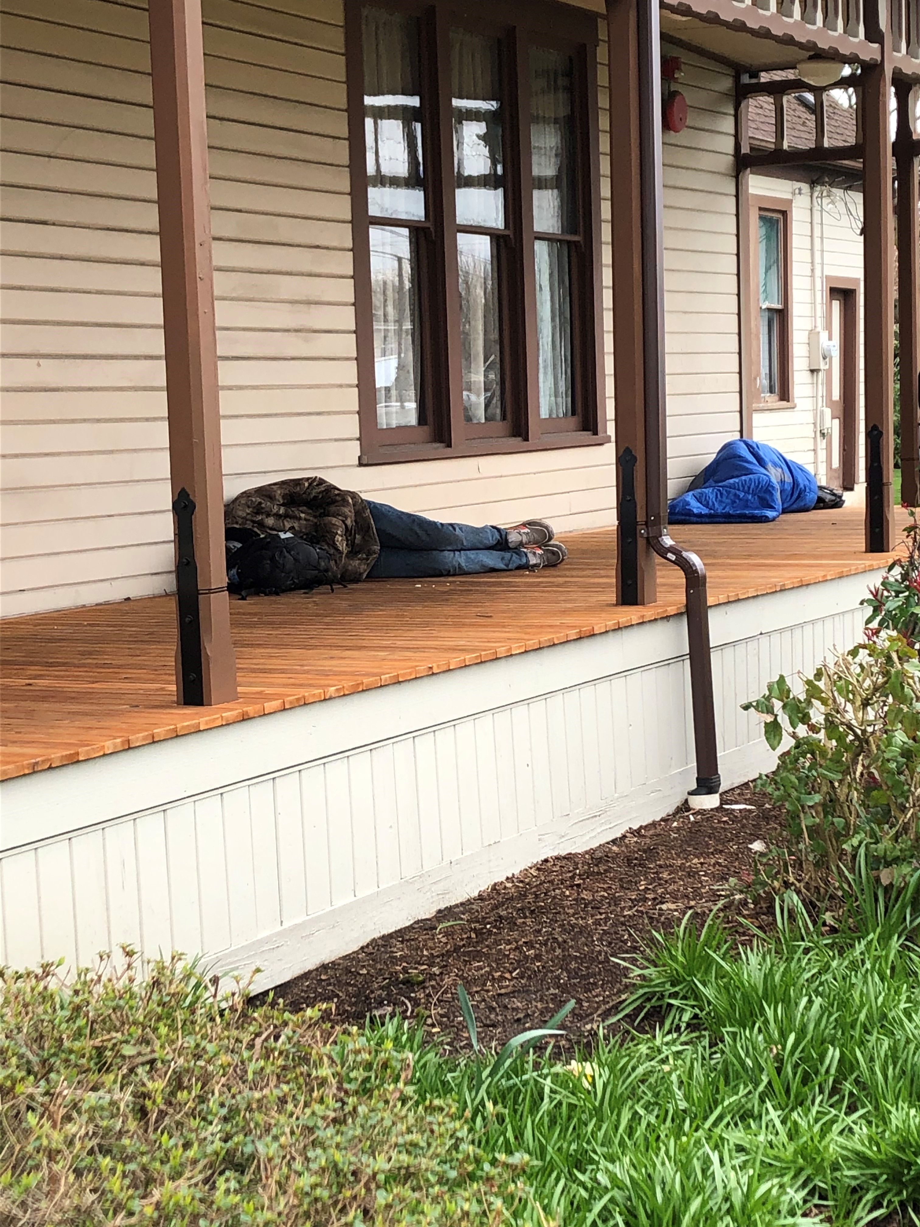 Two people sleeping on the Ryan House porch.