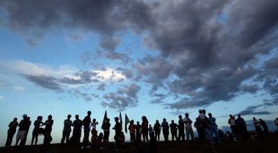 People stand on a hillside behind a memorial for victims Sunday, behind the theater where a gunman opened fire on moviegoers in Aurora, Colo., on Friday.
