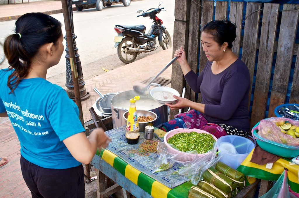 The seller quickly ladled out hot boiled rice soup from a big pot into a bowl