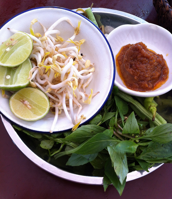 A lot of herbs in a bowl with mint, basil, coriander, chili, lime, bean sprouts and green beans, yes, raw long green beans for your choice