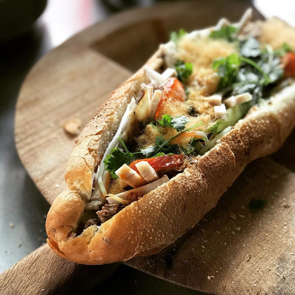 The baguette is cut along its length to open, then filled with pork liver pate, ham, cilantro, cucumbers, carrots, a choice of dressing including mayonnaise, chili sauce and a spicy brown sauce