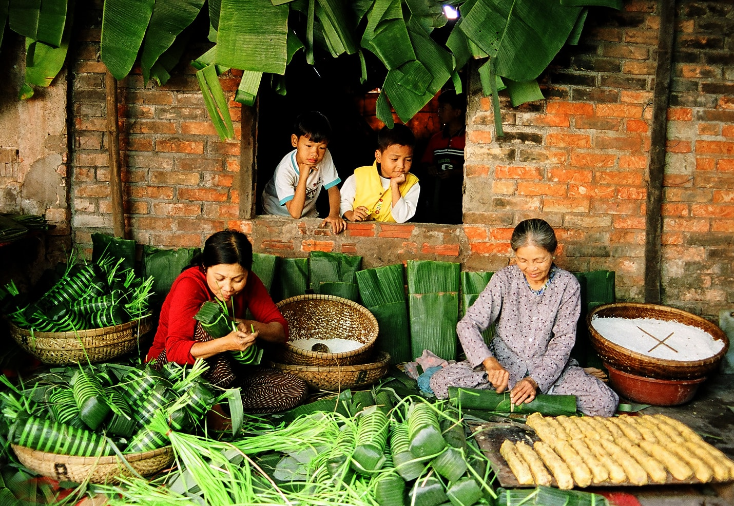 Family members gather to cook Banh Chung or Banh Tet - a special traditional food in New Year festival