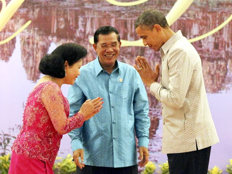 Former U.S. President Obama (right), returns a greeting to Bun Rany, wife of Cambodian Prime Minister Hun Sen (center), prior to a gala dinner in Phnom Penh, Cambodia