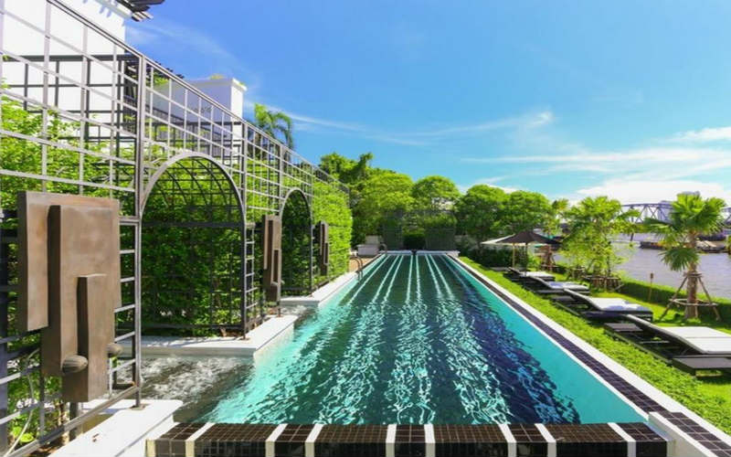 An outdoor swimming pool at The Siam Bangkok overlooks the beautiful Phraya River