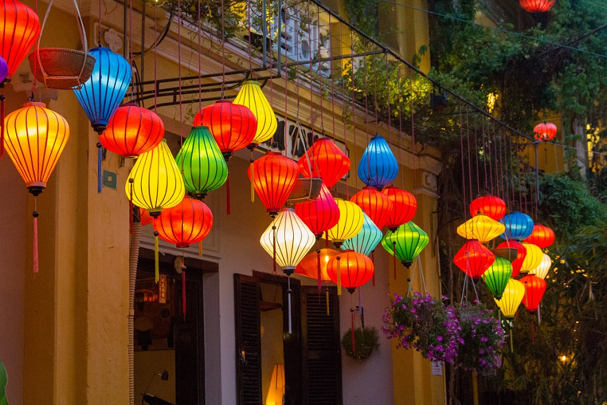 Silk lanterns are hanging in front of boutique shops' doors