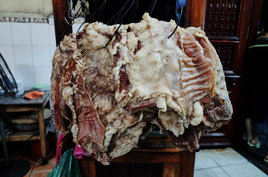 Huge cuts of boiled beef are hanging on the hooks, waiting to be served
