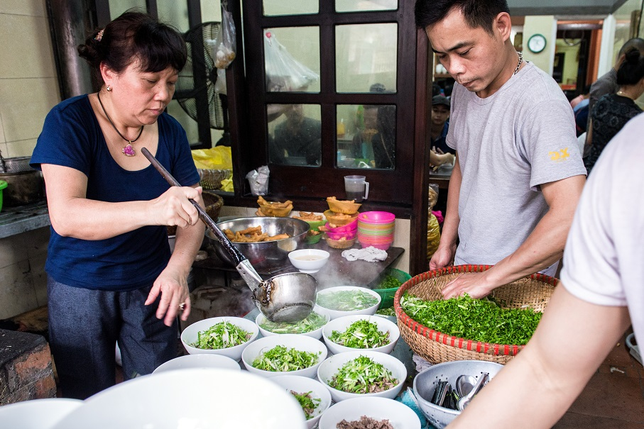 The shop owner is pouring hot broth into Pho bows. Pho has a delicious smell, it can stimulate your appetite very strongly
