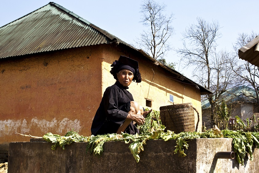 A Ha Nhi woman was sitting next to her house