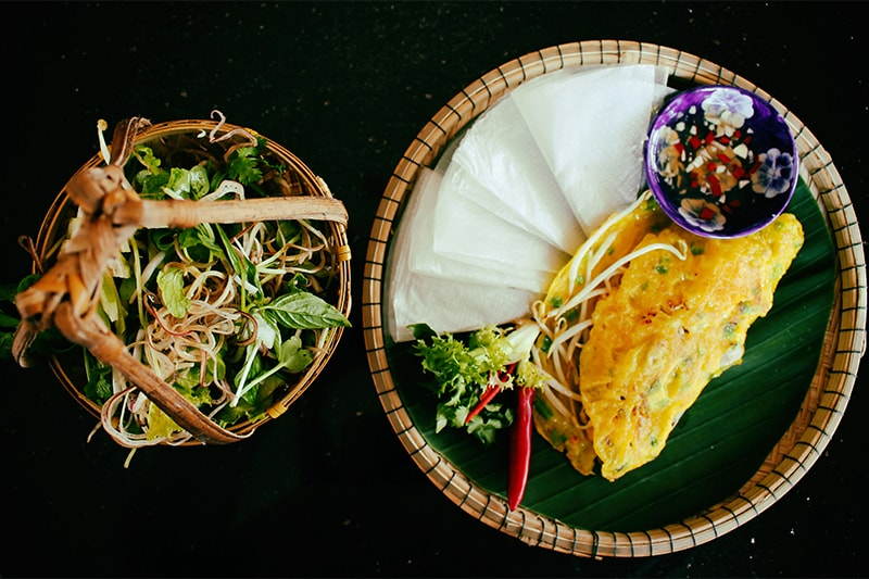 Banh Xeo is often served with fresh herbs and flavorful dipping sauces