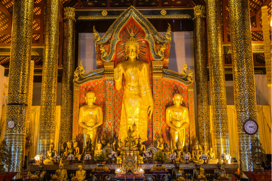 Standing golden Buddha statues inside the temple.