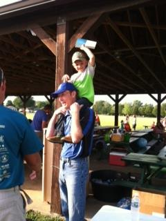 Ethan passing out Bibles on Pastor Tim's shoulders.