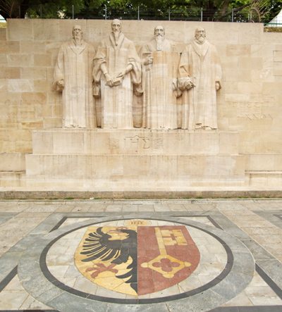 """Sculptures of the four great figures of the geneva protestant movement : Guillaume Farel (1489 - 1565), Jean Calvin (1509-1564), Theodore de Beze (1513-1605) and John Knox (1513-1572) on the reformation wall in Bastions park in front of Geneva flag on the ground, Geneva, Switzerland. The construction of this wall started in 1909. The motto of the Reformation and Geneva is written behind these statues : """"Post Tenebras Lux.""""."""