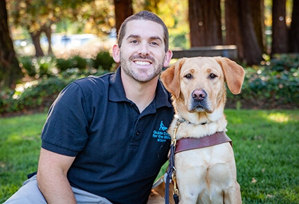 Guide Dog Mobility Instructor Adam Gilbert with a yellow Lab guide dog.