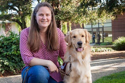 Guide Dog Mobility Instructor Amanda Jones with a smiling Golden Retriever guide dog by her side.