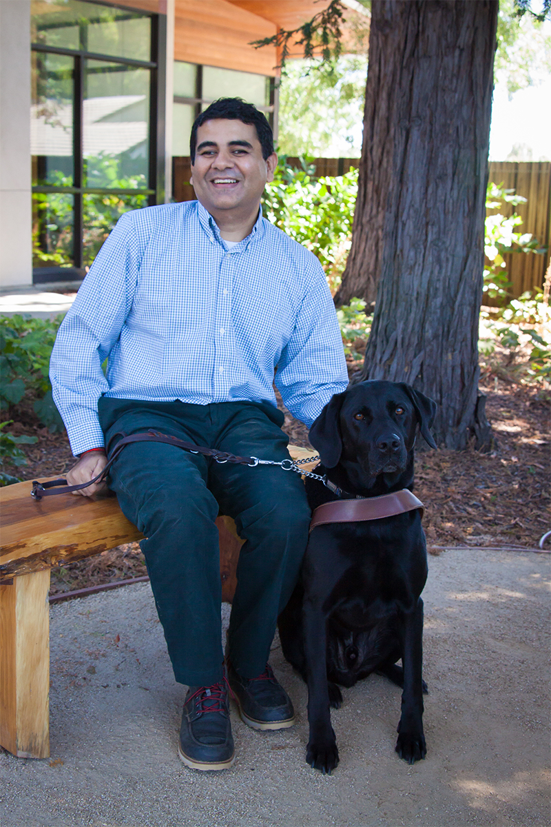 Amit sits on a bench next to his black Lab guide dog Tashi.
