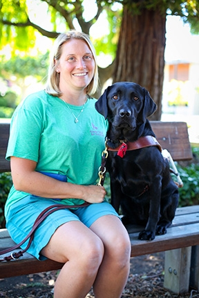 Amy Salger sitting on a bench next to Marsala, her black Lab guide dog.