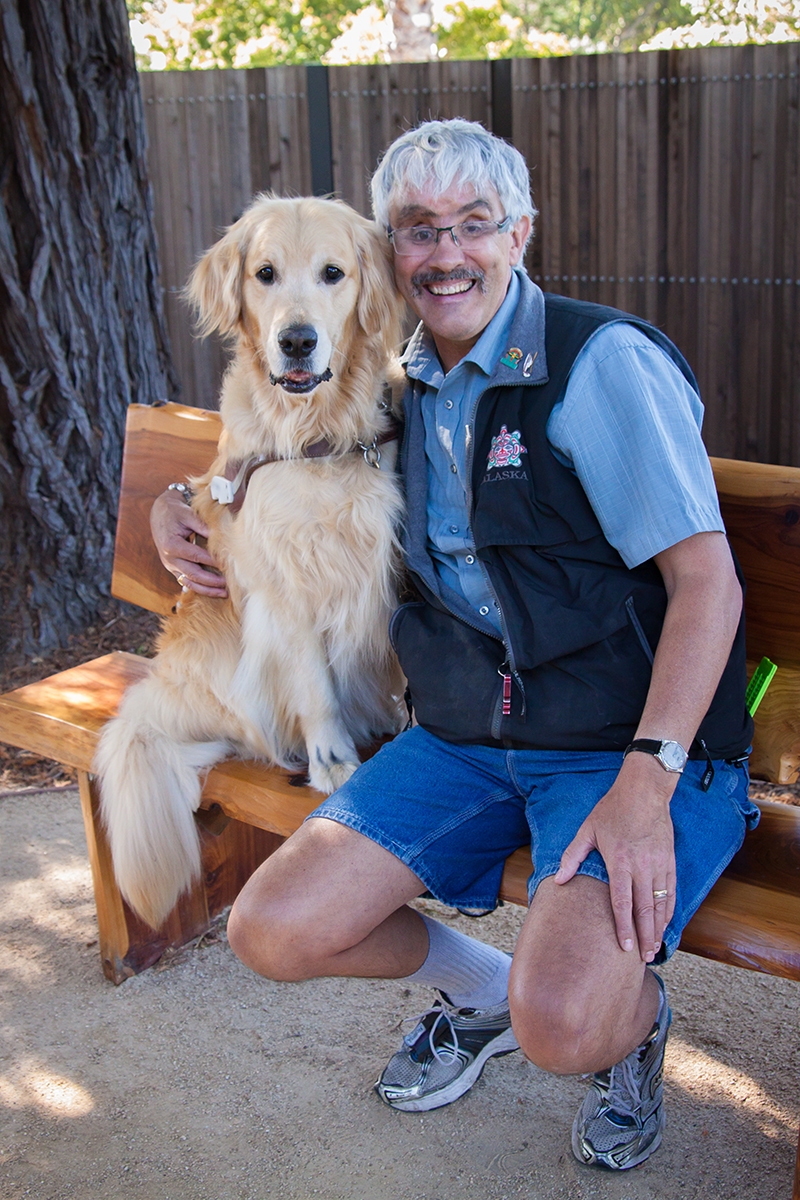 Bruce sits on a bench next to his Golden Retriever guide dog Marley