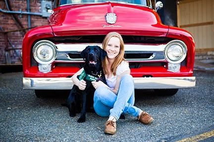 Caitlin poses in front of a vintage red truck with her black Lab guide dog puppy.