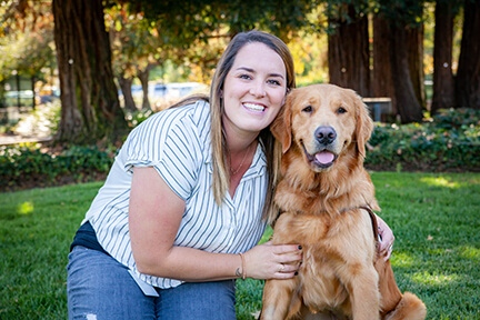 Guide Dog Mobility Instructor Chelsea Adyelott with a Golden Retriever guide dog.