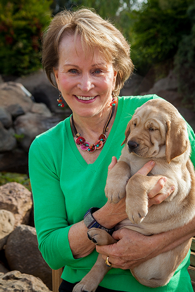 President and CEO Christine Benninger holding a yellow Lab puppy.