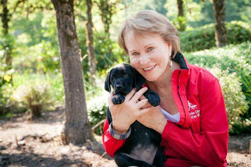 CEO Christine Benninger holding a black Lab guide dog puppy.