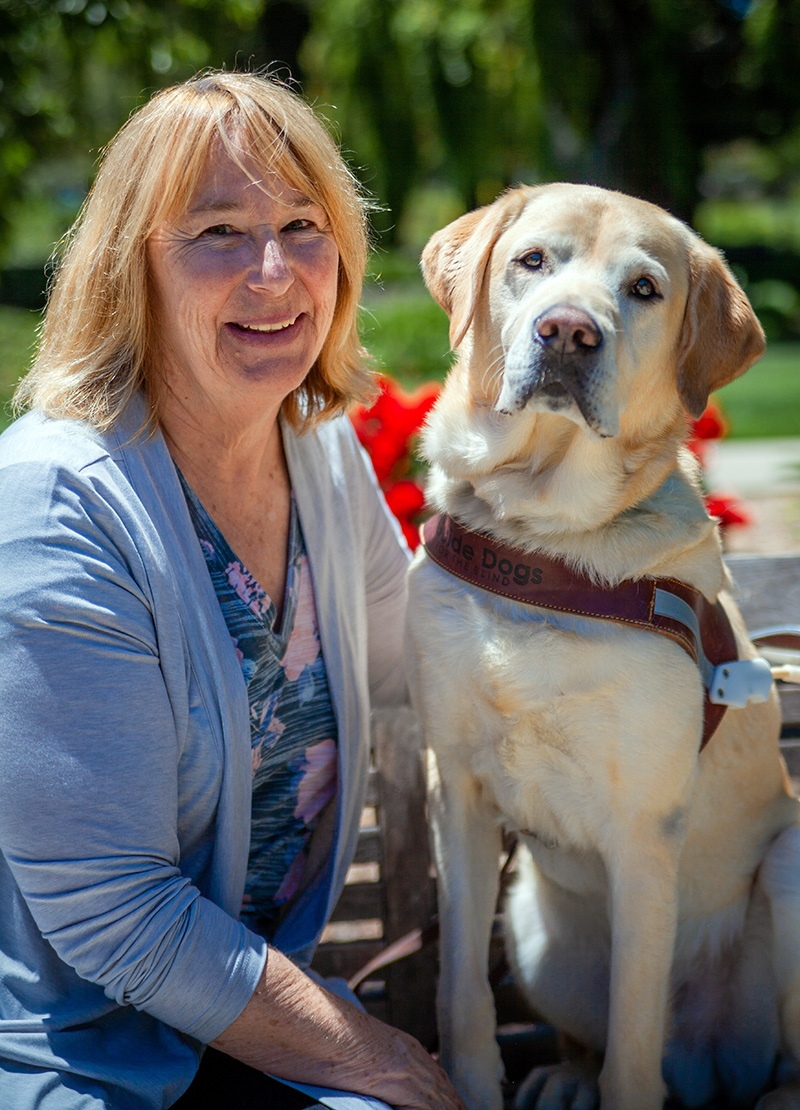 A portrait of Claudia Barkmeier sitting next to a yellow Lab guide dog.