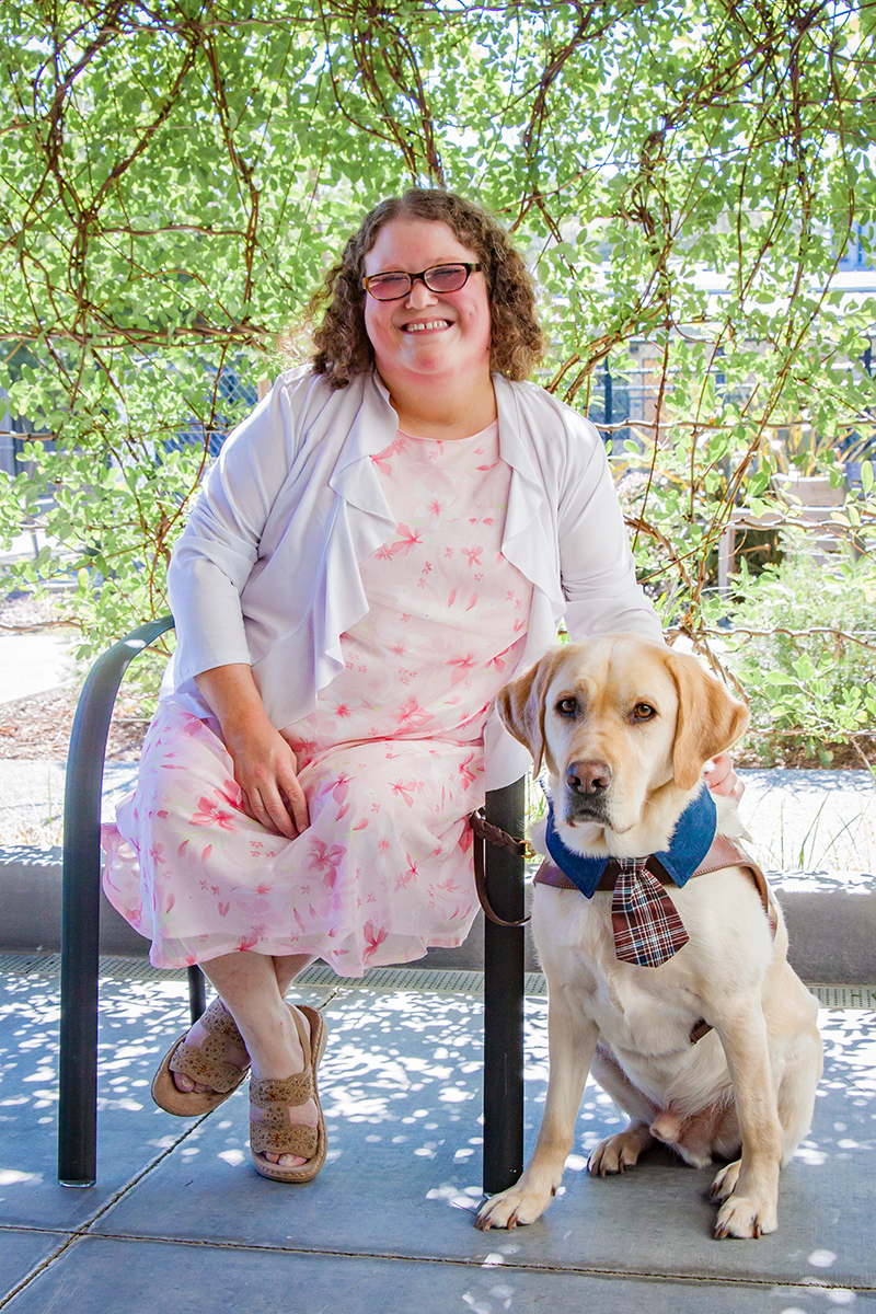 A portrait of Deanna Lewis sitting next to her yellow Lab guide dog, Mambo.