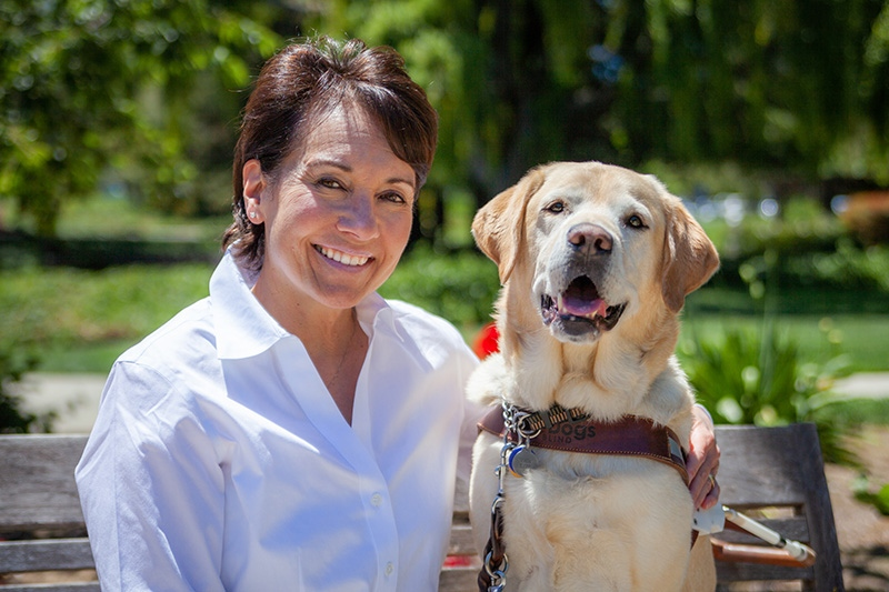A portrait of Diana McQuarrie sitting next to a yellow Lab guide dog.