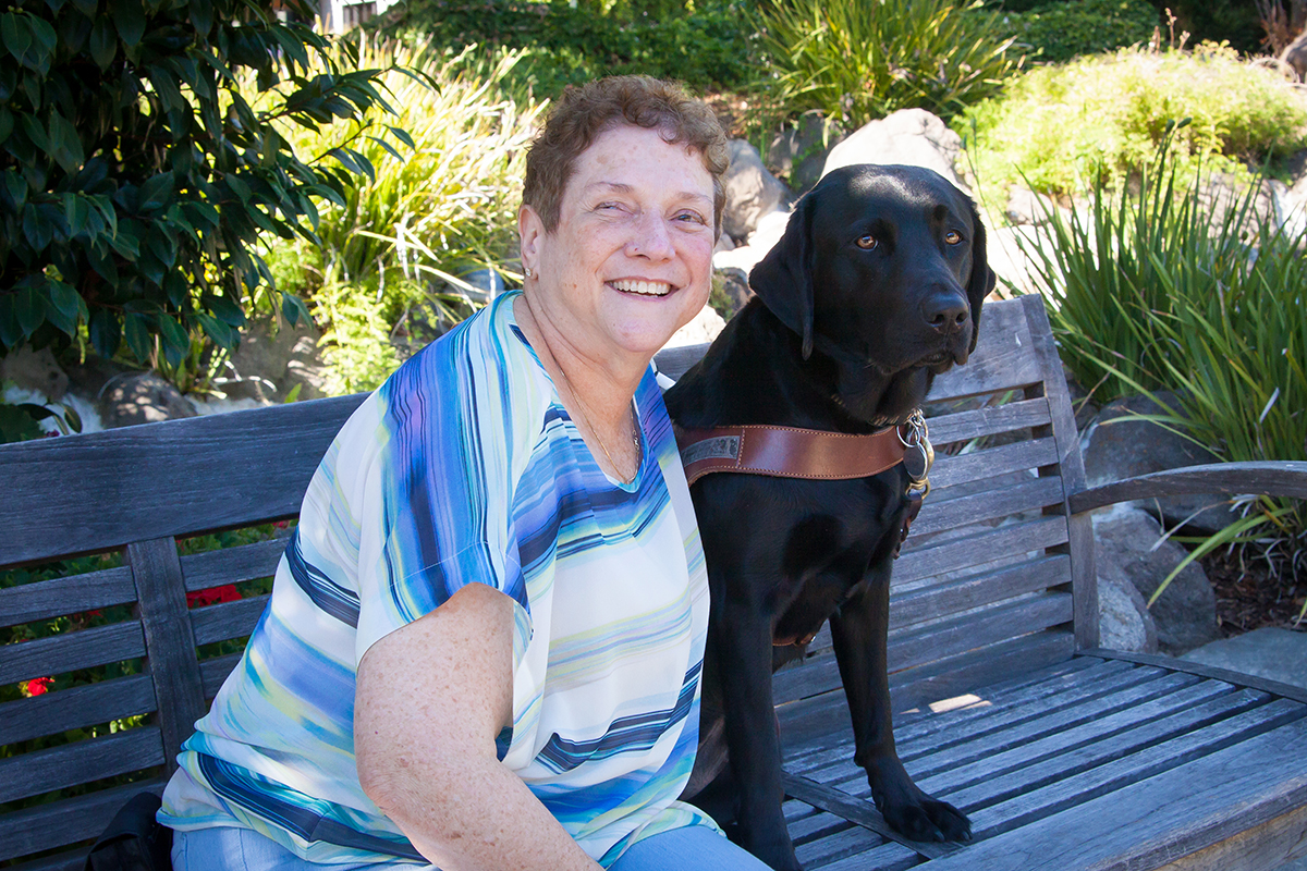 Dorianne sits on a bench next to her black Lab guide dog Dime.