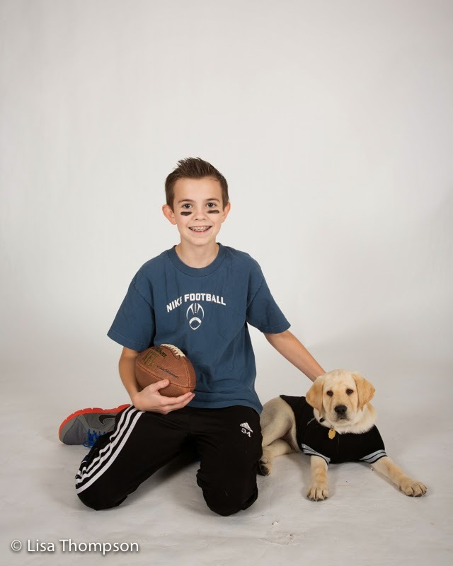 Young yellow lab puppy Will in a black jersey poses with a boy holding a football.