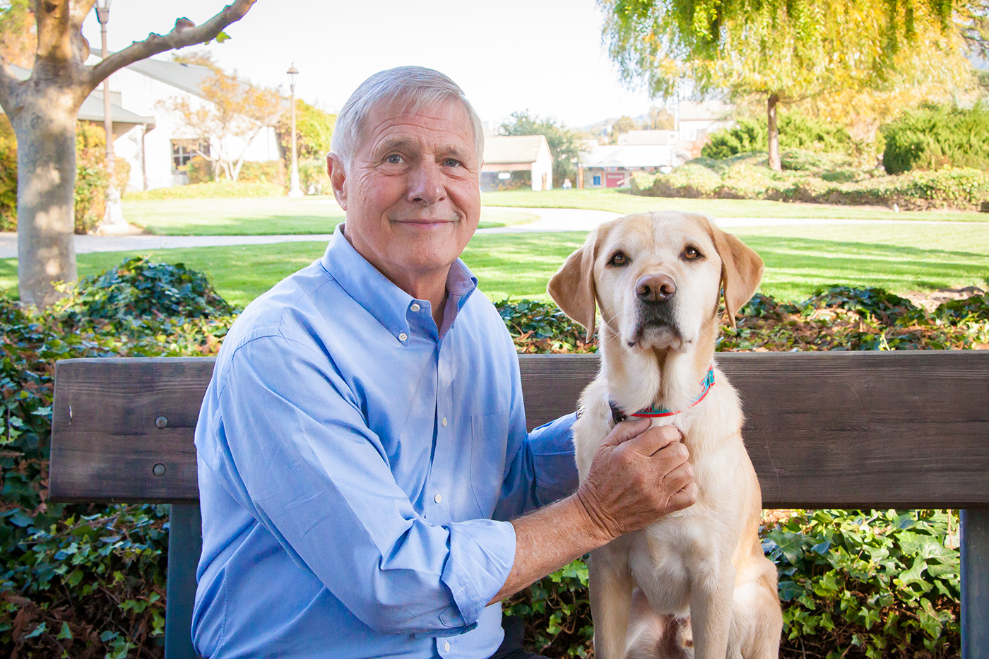 Greg Rice sits on a wooden bench next to a yellow Lab. Green grass and trees are pictured in the background.