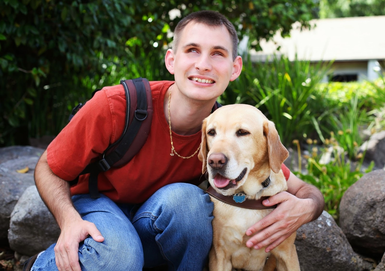 Jake smiles and puts his arm around his guide Angelina (yellow Lab) with rocks and green plants in the background.