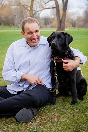 A portrait of Jason Mitschele sitting next to his black Lab guide dog, Kailua.