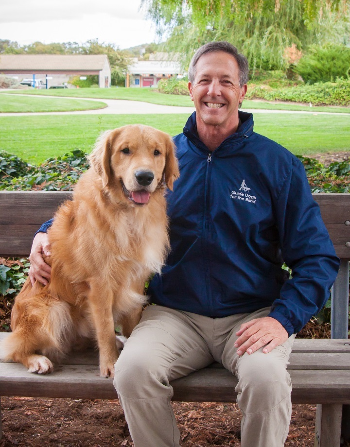 Jeff Grey sitting on a bench next to a fluffy Golden Retriever. Both are smiling at the camera.
