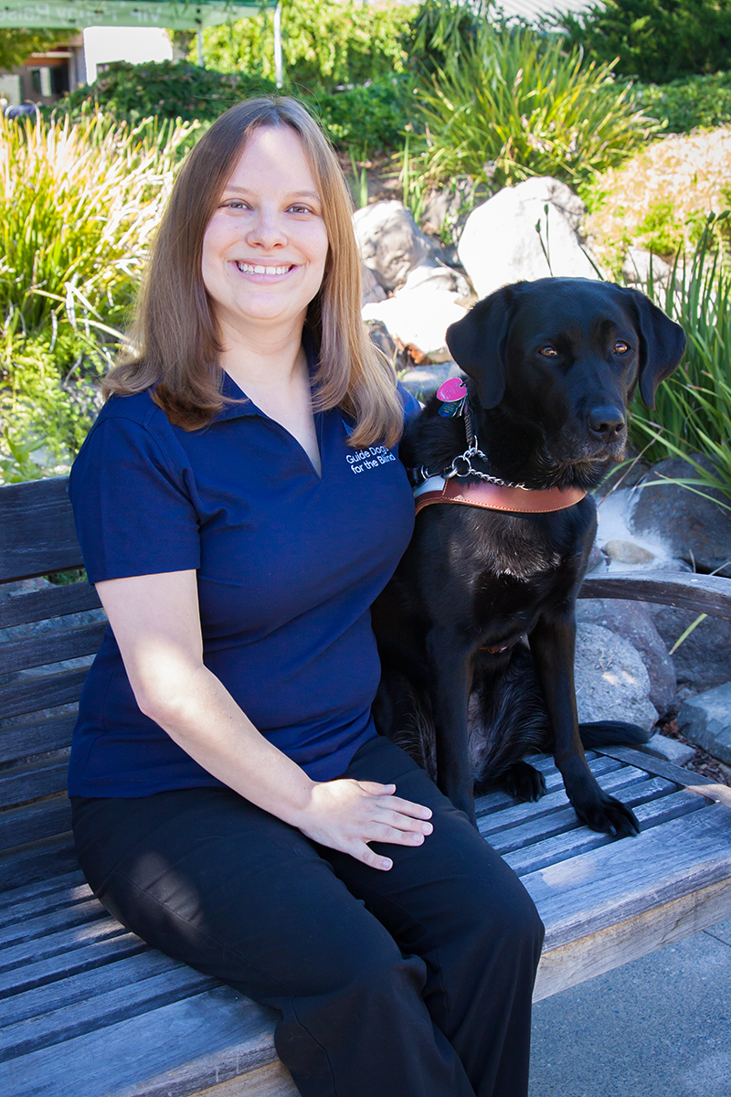 Jessica sits on a bench with her black Lab guide dog Makiko